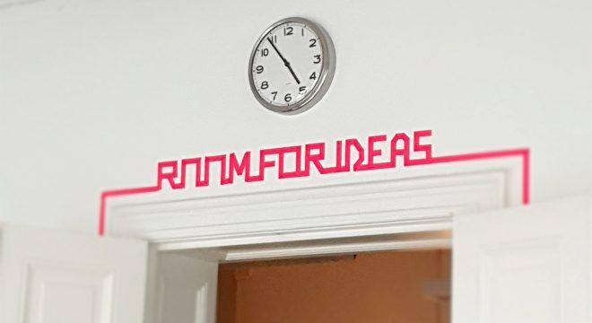 """Zimmertür über der aus Neon-Klebeband die Worte """"Room for ideas"""" geschrieben steht."""